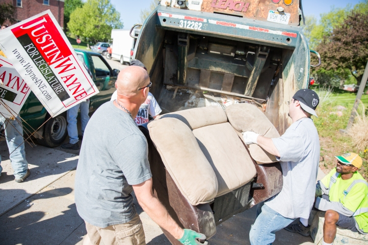 two-volunteers-load-chair-into-garbage-truck